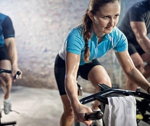 Indoor cycling class with woman focused on riding hard