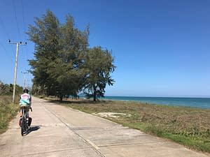Cycling along the beach front at Baan Krud Thailand