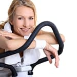 Woman resting on stationary bicycle, smiling while taking a break