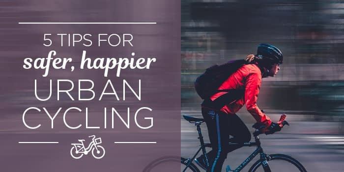 cyclist riding past blurred city buildings - tips for urban cycling