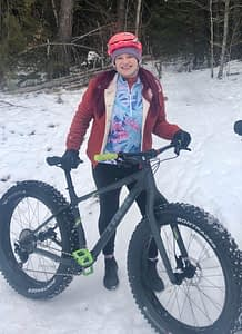 Cam wears Terry and poses with her rented fat bike on a snowy trailhead