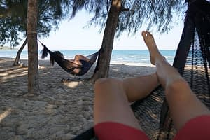 Pausing for a mid-day rest in hammocks on the beach, Baan Krud Thailand