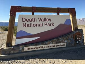 Sign marking the entrance to Death Valley National Park, California, with mountains in the background