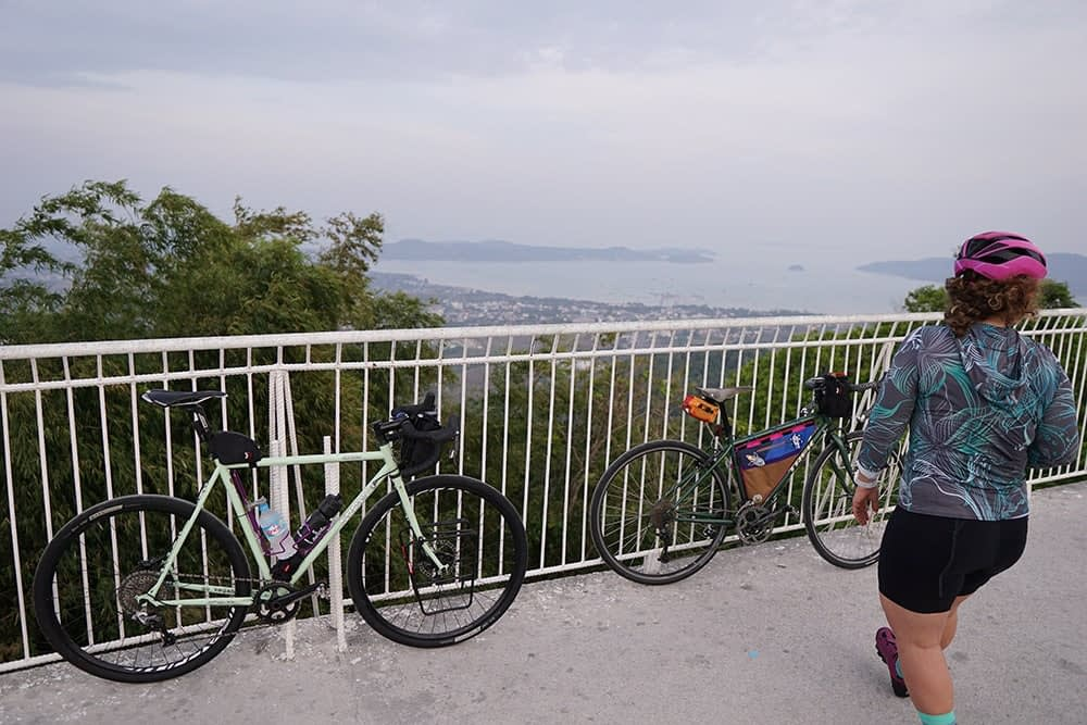 Bikes leaning on a railing as we enjoy a view over the ocean from a high spot on Big buddha Phuket island off southern Thailand