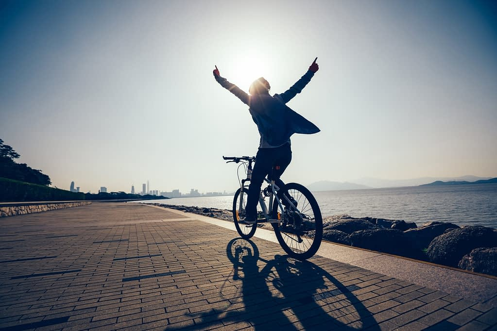 Woman cycling alongside a river, cityscape in the far distance, holding arms up joyfully