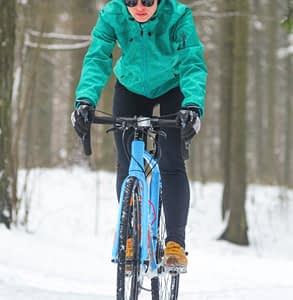 Woman cycling on trails in winter on a gravel bike.