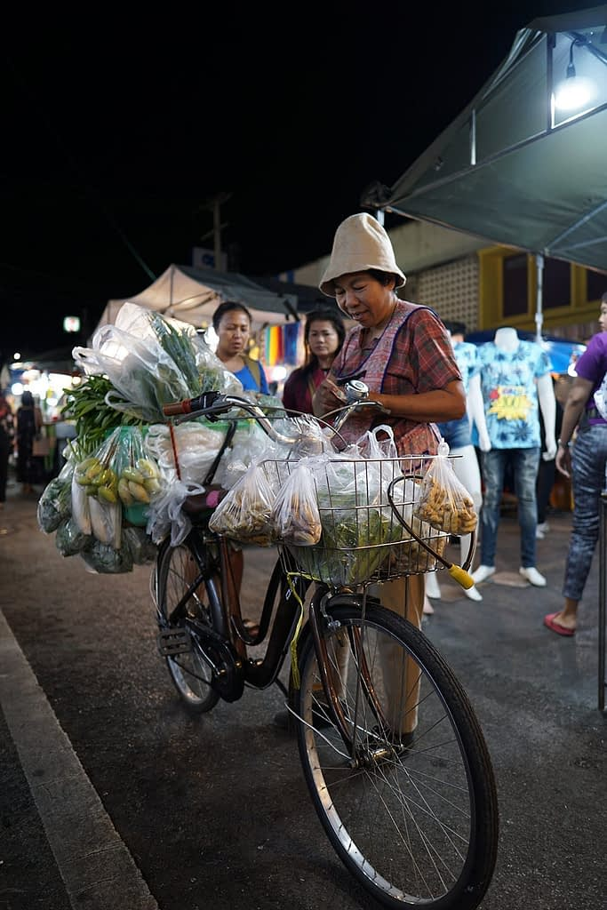 A woman sells vegetables from her bicycle, in a night market in Hua Hin, Thailand