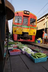A train makes its way along a narrow street lined with market stalls and produce, pulled quickly out of the way as the train passes.