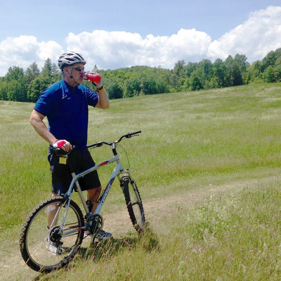 Celebrating cycling dads on father's day – Photo of Rob taking a breather while mountain biking at on Vermont's Kingdom trails