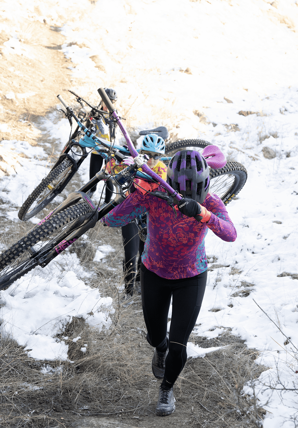 Women shouldering their mountain bikes to climb a hill, snow on ground, wearing Terry bike jerseys and cycling tights