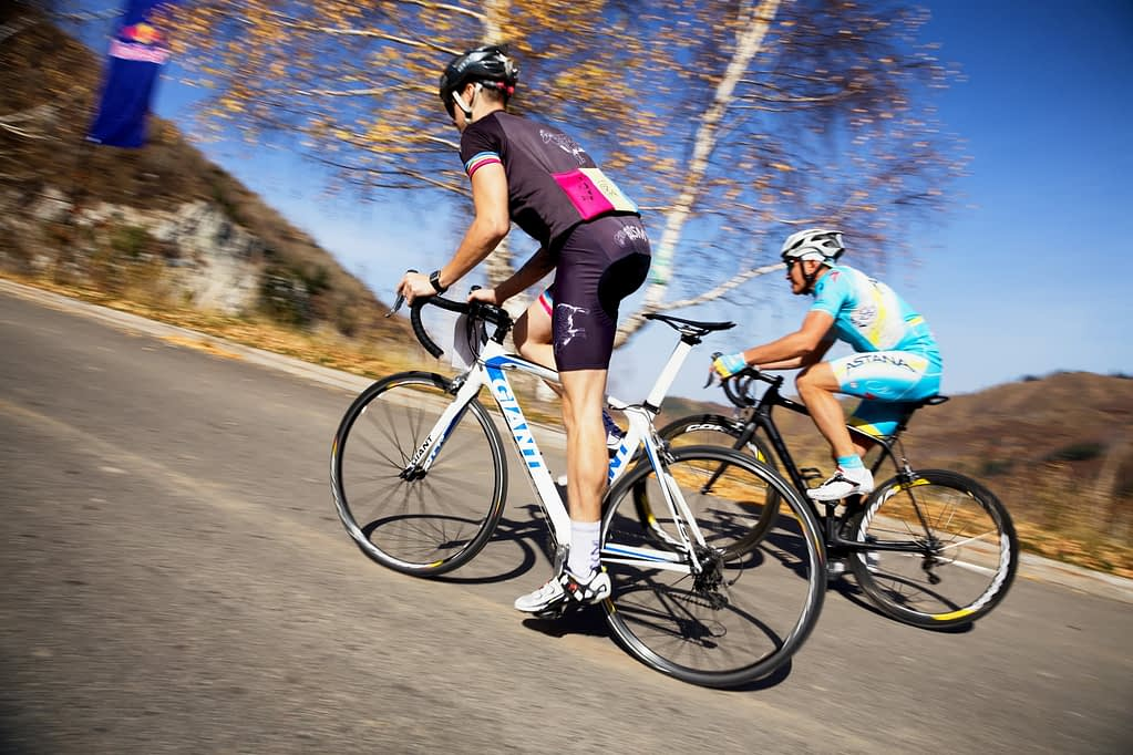 two cyclists climbing a steep hill, one still seated, the other standing on the pedals