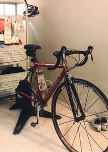 Lisa's indoor cycling setup, with bike on stationery stand in her office, and shelves of bike gear near at hand