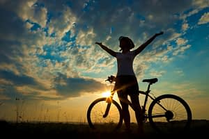 cyclist pauses to celebrate with arms in the air and a beautiful sunset