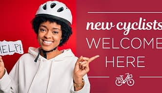 woman in cycling helmet with hand made sign reading help, and text overlayed reading new cyclists welcome here