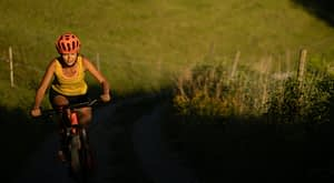 Woman riding uphill in countryside in sunset lighting
