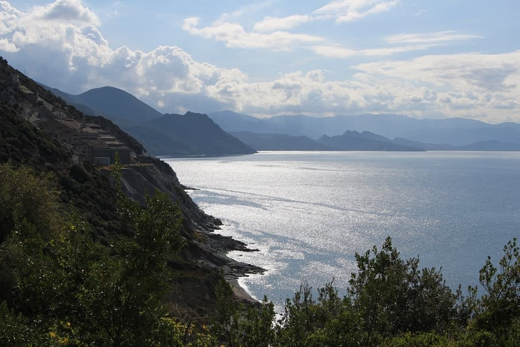 View of coastline in Corsica, with mountains in the distance sunlight shimmering on the sea