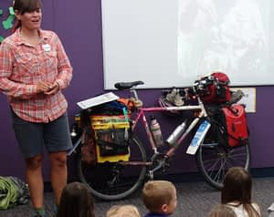 Sara with her fully laden touring bike giving a presentation to a kindergarten class.