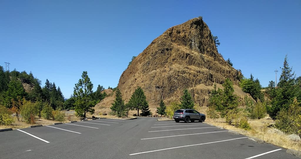 Photo of the trailhead of the Historic Columbia River Highway Trail, showing the nealy empty car park and a dramatic rock outcropping.