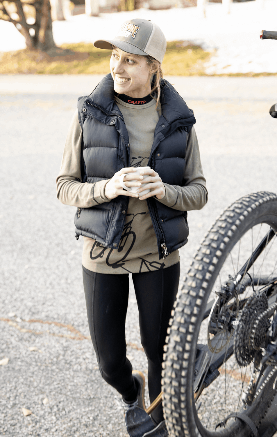 Woman warming up after a ride with a hot drink, bike back on rack, wearing Terry Coolweather Tights.