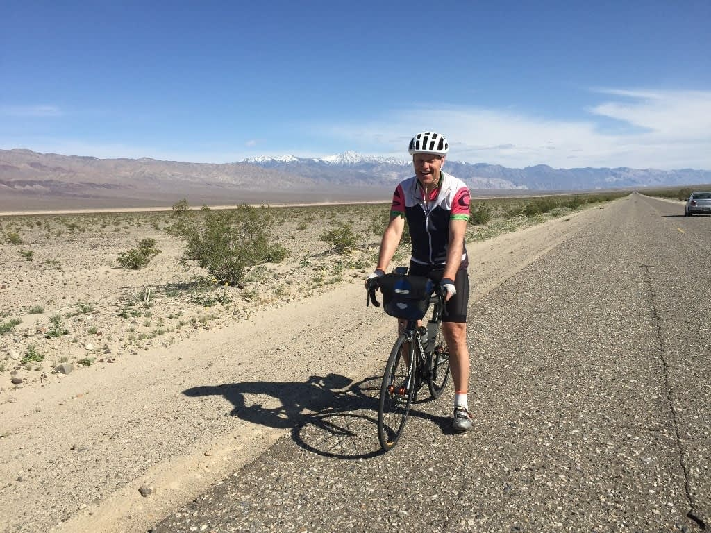 Chris cycling in Death Valley California, on a long strip of road on the valley floor, snow capped mountains in the background
