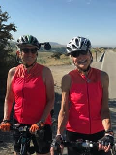 Bonnie V. with friend riding in hot weather in Bogus Basin Idaho, wearing matching red Hale Glow cycling tops from Terry Bicycles