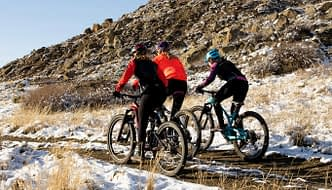three female cyclists riding through a wintry landscape during a field test of women's cycling tights
