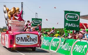 photo of a motorized float in the tour de france caravan, with free packages of biscuits being thrown to an enthusiastic crowd