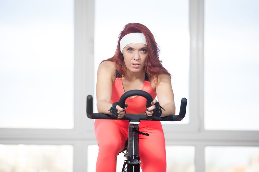 Woman riding an indoor stationery bike with a determined expression