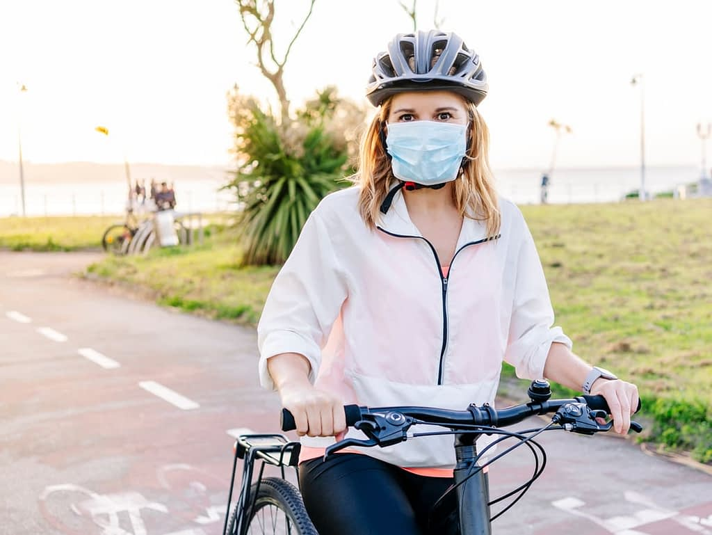 Woman paused during bike ride, wearing face mask during covid-19 pandemic