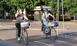 two women cyclists riding in a bike lane wearing face masks