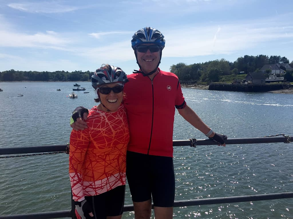 BikeMaine tour 2019 - Deb and Charlie pose with a sparkling seaside view