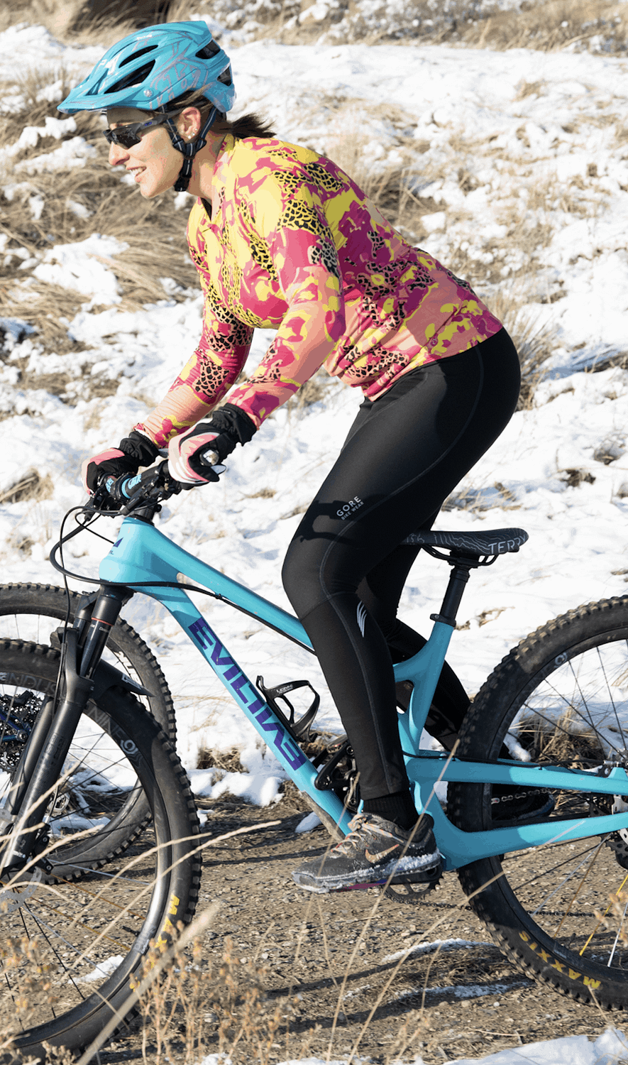 Woman riding a mountain bike in a snowy landscape, wearing Terry cycling top and windproof cycling tights