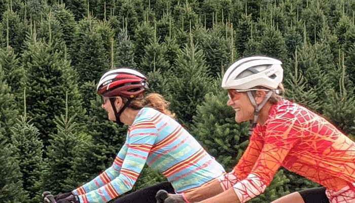 Two women cycling past a christmas tree farm in Vermont