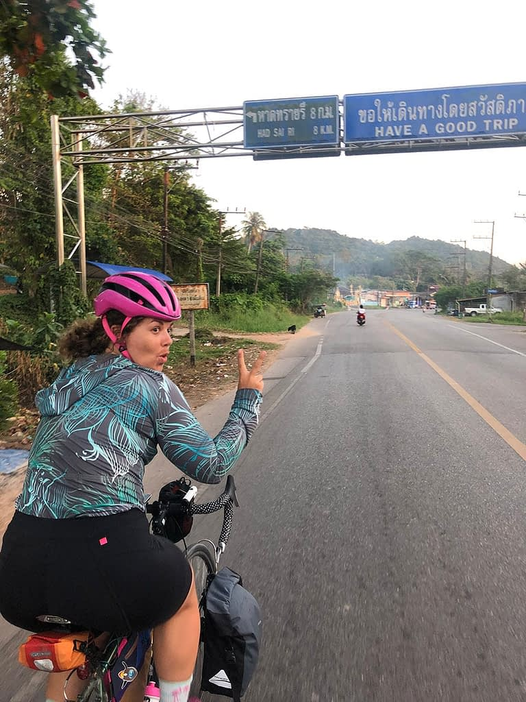 Riding under a bilingual road sign with the message Have a good trip, Thailand