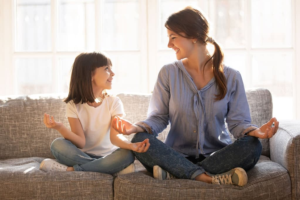 Mom and daughter share a laugh while practicing mindfulness on the couch