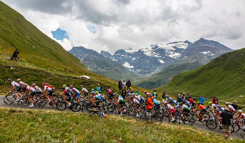 Peloton rides up a mountain road with soaring peaks in teh background, Tour de France 2019