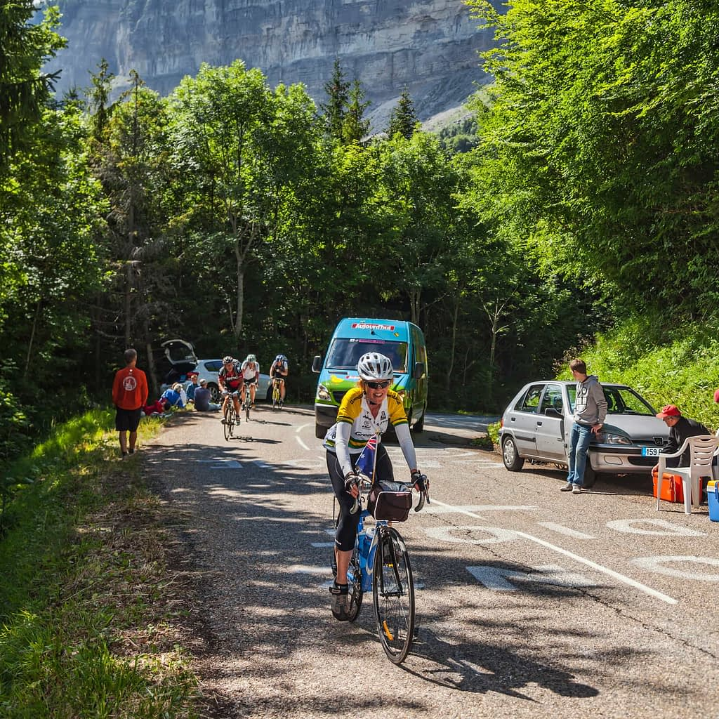 cycling climbing tip about how to ride up long hills - Woman climbing a mountain road on a race route in France, ahead of other cyclists.