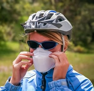 A cyclist adjusting her face mask ready for cycling