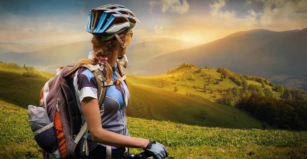 Woman pausing to admire a beautiful sunset view over a lush mountain landscape, at the finish of a long climb on her bicycle.