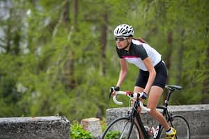 cycling climbing tip about how to ride uphill standing on the pedals – Woman cycling up a hill with good out of the saddle technique