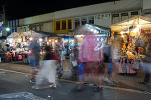 Street scene at a night market, Thailand. Shoppers pass brightly lit stalls.