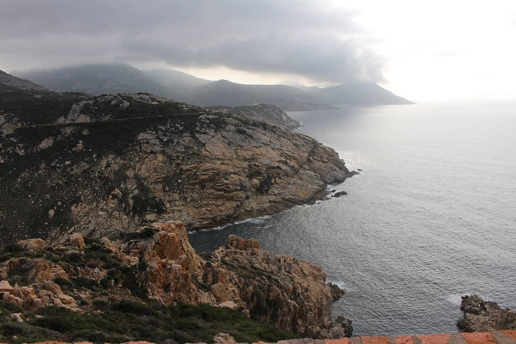 Dramatic mountains loom over the sea in Corsica