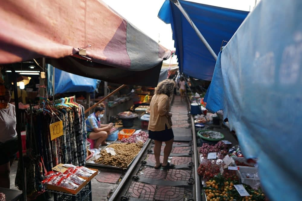 Walking along the tracks in the Mae Khlong Train market, Thailand