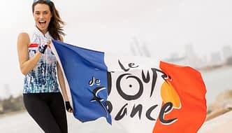 Model wearing Terry cycling clothing, holding a flag celebrating 2020 Tour de France.