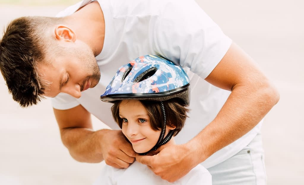 A man securing a bike helmet on a child's head. It does not appear to be sized correctly, and he could use some tips on how to fit a bike helmet properly.