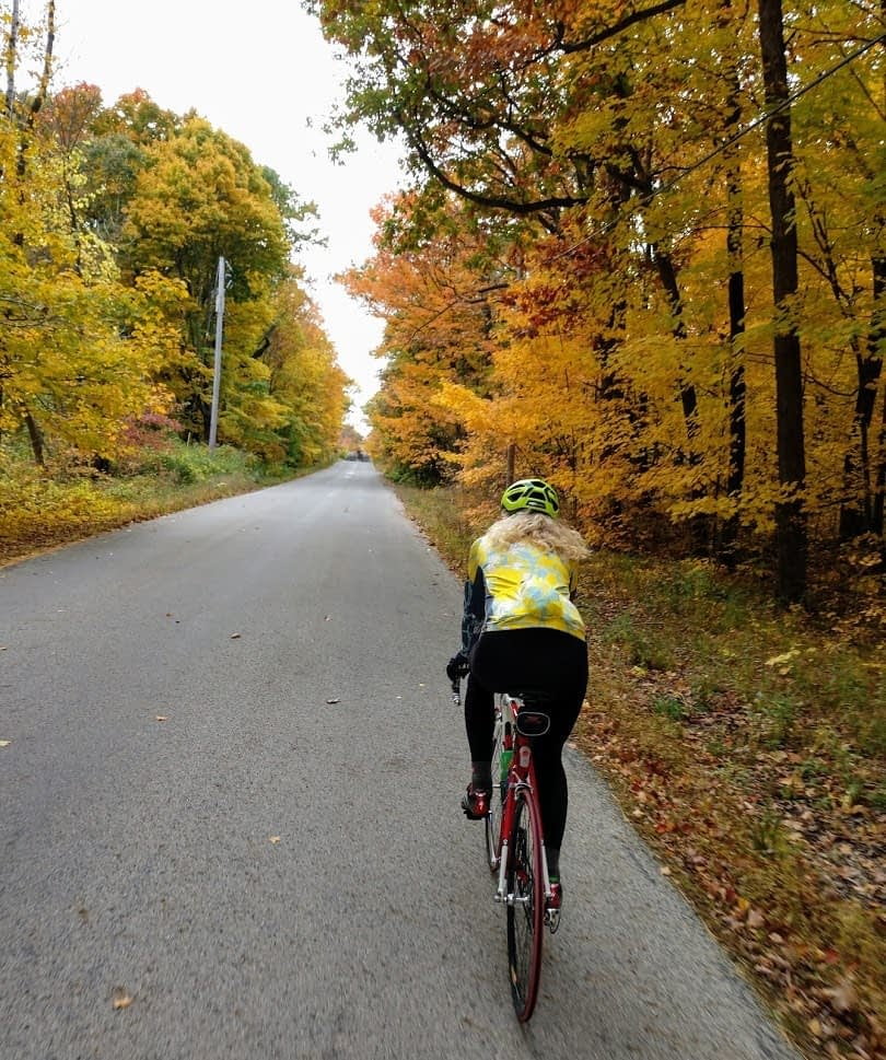 Tracy Flucke rides along a lane lined with fall foliage