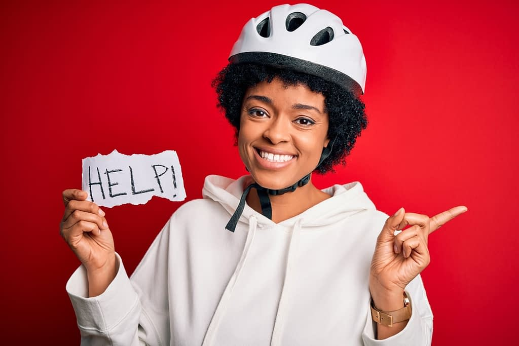 womain in cycling helmet with hand made sign reading help, and text overlayed reading new cyclists welcome here