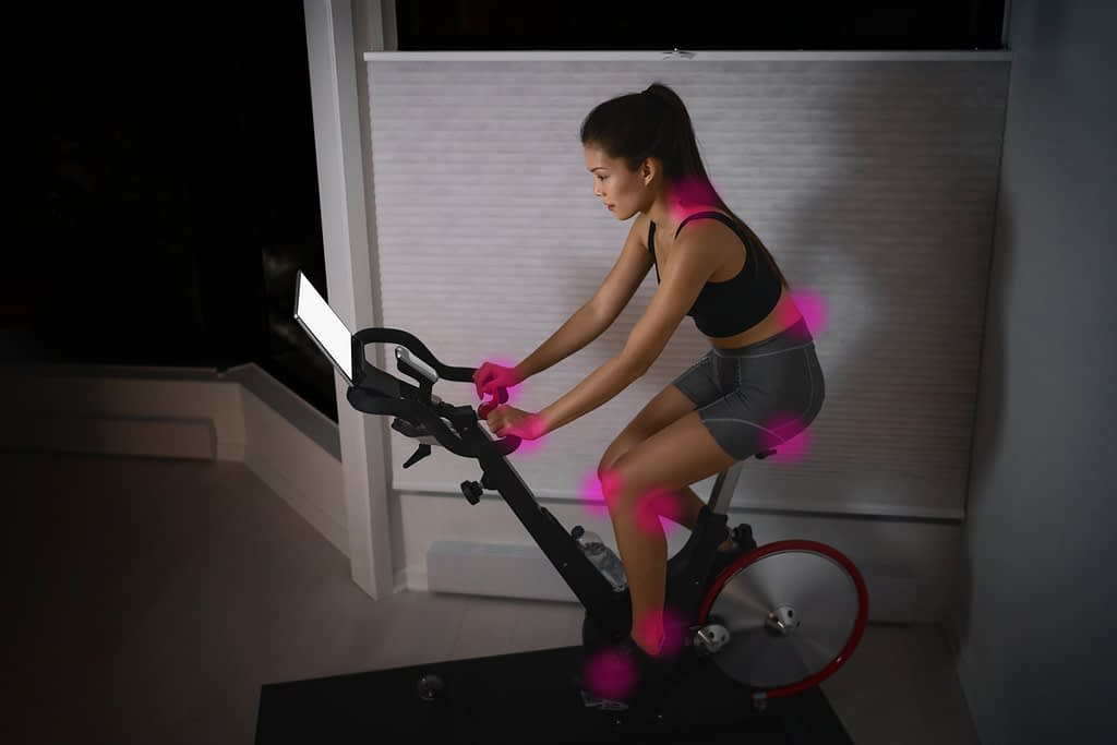 Woman riding an indoor exercise bike or peloton bike, with highlights showing pain points from incorrect riding position